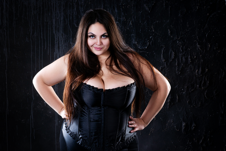 Sexy plus size model in black corset, fat woman with big natural on dark background, body positive concept, studio shot