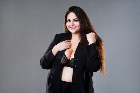 Feliz modelo de moda de talla grande en ropa, mujer gorda sobre fondo gris de estudio, concepto de cuerpo positivo, tiro del estudio