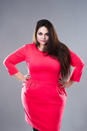 Plus size fashion model in red dress, fat woman on gray studio background, body positive concept