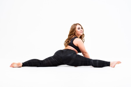 Plus size model in sportswear, fat woman doing workout on white studio background, body positive concept
