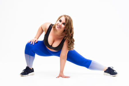 Plus size model in sportswear, fat woman doing workout on white studio background, body positive concept 写真素材 - 121760127