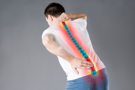 Pain in the spine, a man with backache, injury in the human back, chiropractic treatments concept with highlighted skeleton