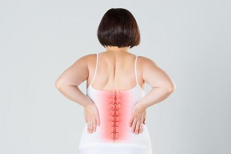 Dolore alla colonna vertebrale, una donna con mal di schiena, lesioni alla schiena umana, concetto di trattamenti chiropratici con scheletro evidenziato