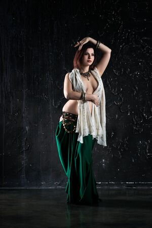 Sexy women performs belly dance in ethnic dress on black background, abstract art photography, studio shot