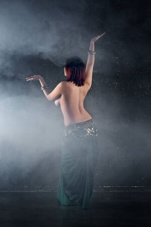 Sexy women performs belly dance in ethnic dress on dark smoky background, abstract art photography, studio shot