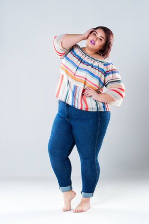 Plus size fashion model in casual clothes, fat woman on gray studio background, body positive concept