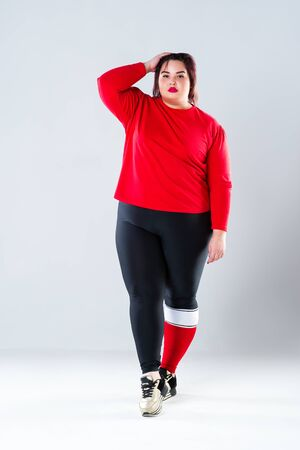 Plus size model in sportswear, fat woman doing workout on gray studio background, healthy lifestyle concept, body positive 写真素材