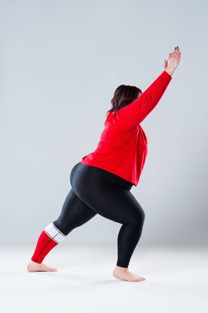 Plus size model in sportswear, fat woman doing workout on gray studio background, healthy lifestyle concept, body positive Stock Photo