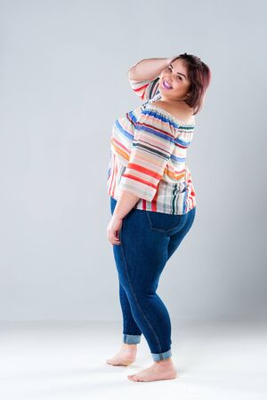Happy plus size fashion model in casual clothes, fat woman on gray studio background, body positive concept