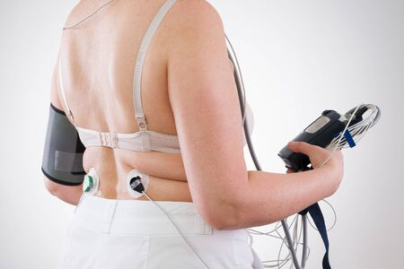 Woman with holter monitor device for daily monitoring of electrocardiogram and blood pressure on gray background