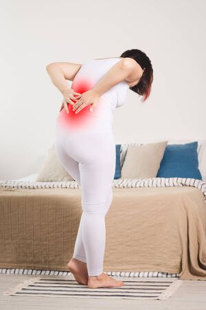 Back pain, kidney inflammation, woman suffering from backache at home, painful area highlighted in red
