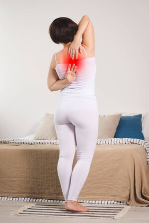 Back pain, woman suffering from backache at home, painful area highlighted in red