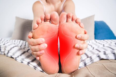 Womans legs hurts, pain in the foot, massage of female feet at home Фото со стока