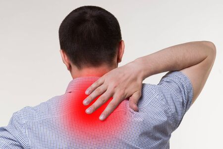 Neck pain, man suffering from backache, painful area highlighted in red Фото со стока