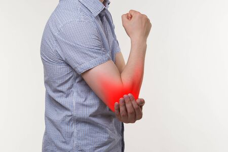 Man suffering from pain in elbow, joint inflammation, painful area highlighted in red