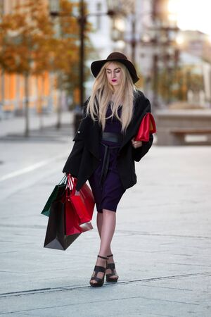Stylish woman with shopping bags walking down the street, holiday concert