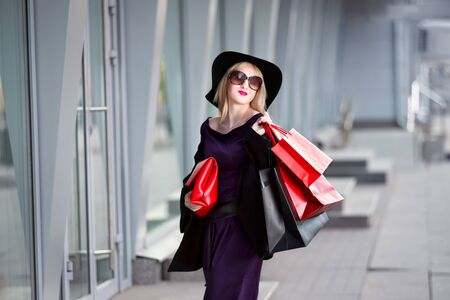 Stylish blonde woman in black coat, sunglasses and hat with shopping bags walks along the street, holiday concert Фото со стока