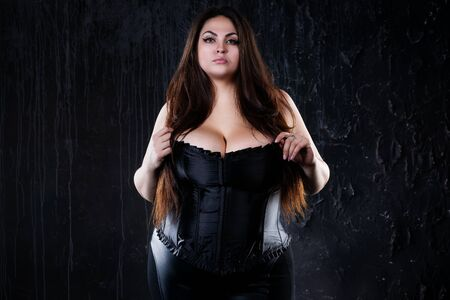Sexy plus size model in black corset, fat woman with big natural breasts on dark studio background, body positive concept