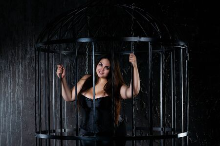 Plus size fashion model in clothes in a steel cage, fat woman in captivity, body positive concept