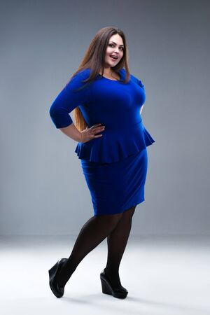 Happy plus size fashion model in blue dress, fat woman on gray studio background, body positive concept, full length portrait