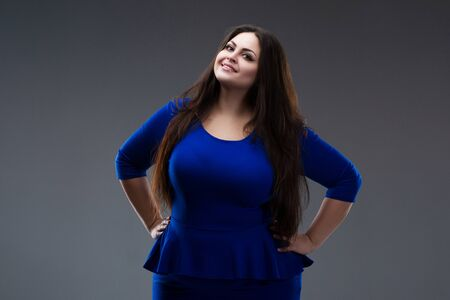Happy plus size fashion model in blue dress, fat woman on gray studio background, body positive concept