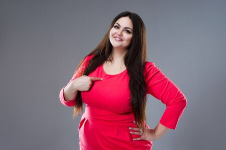Happy plus size model in red dress, fat woman with long hair on gray studio background, body positive concept