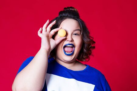 Plus size model with wide open mouth and blue lipstick posing with macaroon on red background, body positive concept
