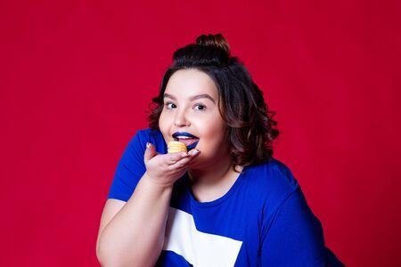 Plus-Size-Modell, das Makronen auf rotem Hintergrund isst, fettes Mädchen liebt Süßigkeiten, positives Körperkonzept Standard-Bild