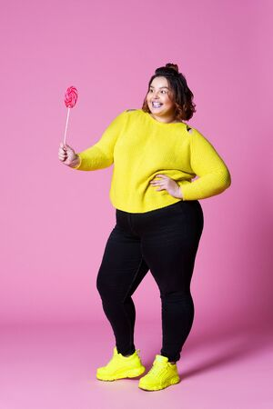 Cheerful plus size model in casual clothes with big lollipop, fat woman in black jeans and yellow jumper on pink background, body positive concept, full-length portrait