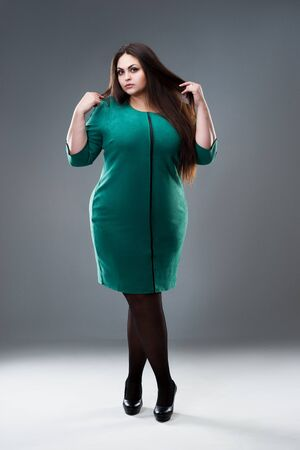Plus size model in green dress, fat woman with long hair on gray