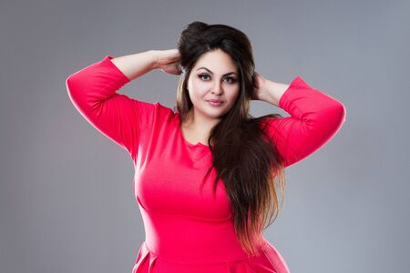 Happy plus size model in red dress, fat woman with long hair on gray