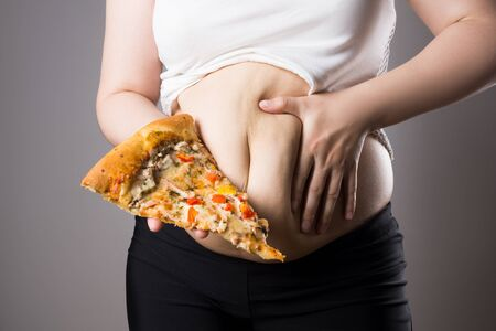 Fat woman with a piece of pizza on gray background, unhealthy nutrition concept Banco de Imagens