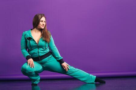 Plus size model in sportswear, fat woman on purple background, body positive concept