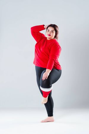 Plus size model in sportswear, fat woman doing workout on gray background, healthy lifestyle concept, body positive