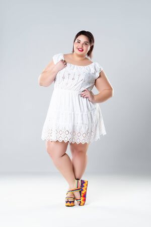 Plus size fashion model in white dress, fat woman on gray studio background, body positive concept