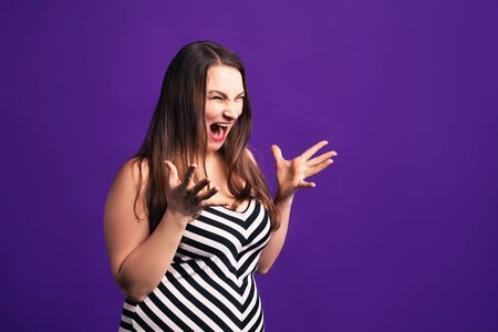 Shocked plus size model with wide open mouth on purple background, body positive concept 版權商用圖片