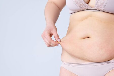 Tummy tuck, flabby skin on a fat belly, plastic surgery concept on gray background with copy space Banco de Imagens