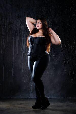 Plus size model in clothes, fat woman on dark background, overweight female body, full length portrait Foto de archivo