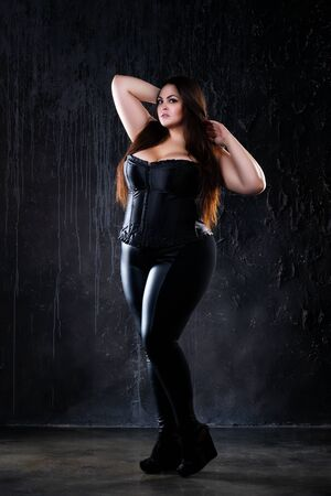 Plus size model in clothes, fat woman on dark background, overweight female body, full length portrait