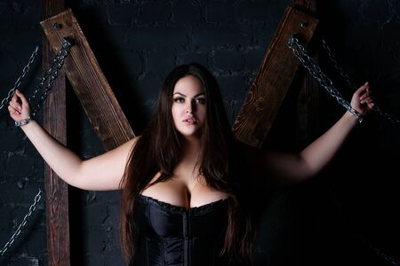 Plus size model tied with chains to a wooden cross, fat woman in clothes, love game and concept