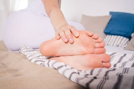 Woman's leg hurts, pain in the foot, massage of female feet at home
