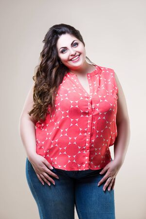 Happy plus size fashion model in casual clothes, cheerful fat woman on beige background, body positive concept