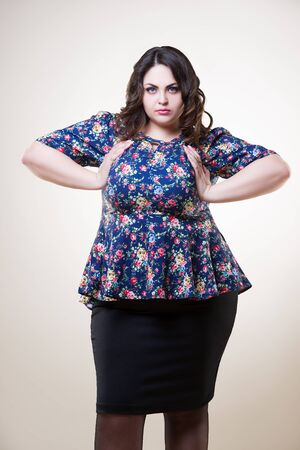 Plus size fashion model in floral blouse, fat woman with big on beige background, body positive concept Stockfoto
