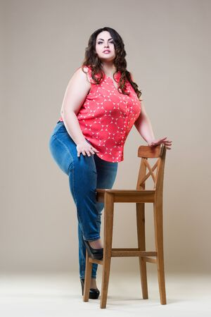 Plus size fashion model in casual clothes, cheerful fat woman on beige background, body positive concept Stock fotó
