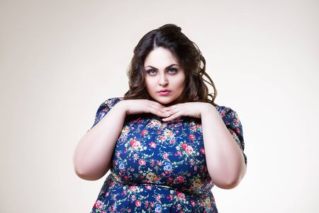 Plus size fashion model in floral blouse, fat woman on beige background, body positive concept