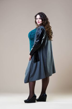 Plus size fashion model in a coat, fat woman on beige background, body positive concept, full length portrait