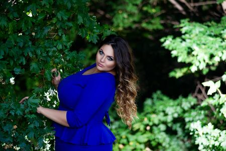 Sexy plus size fashion model in blue dress outdoors, fat woman with beauty makeup and hairstyle, body positive concept Archivio Fotografico