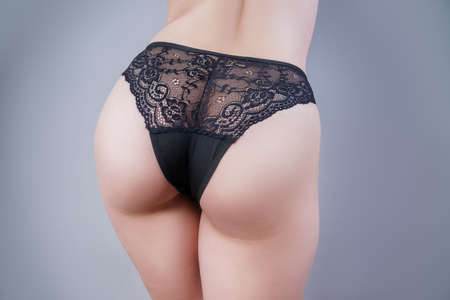 Sexy panties on a perfect female buttocks, gray background Banque d'images