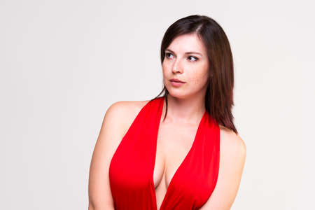 Sexy woman in red dress with deep neckline in studio on gray background,