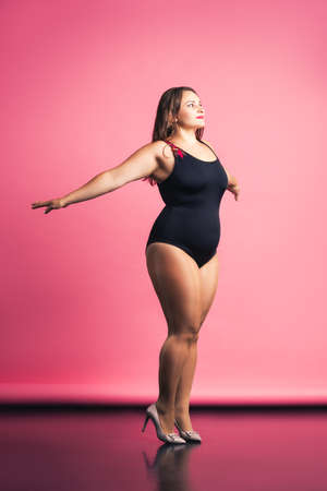Plus size fashion model in black one-piece swimsuit, fat woman in lingerie on pink background, body positive concept Standard-Bild